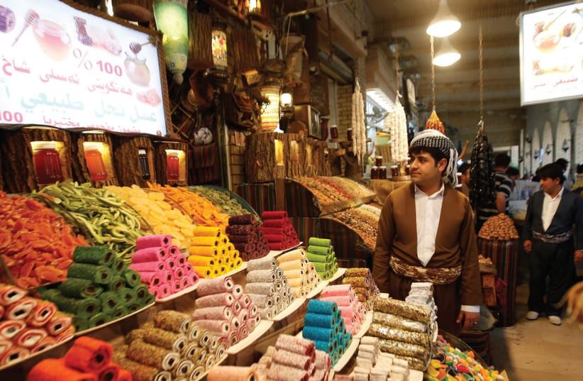 A KURDISH MAN sells sweets at a market in Erbil, the capital of Iraq's Kurdistan region. (photo credit: AZAD LASHKARI / REUTERS)