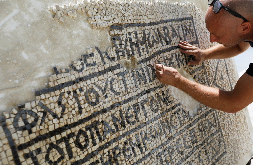 A conservationist works on a 1500-year-old mosaic floor bearing a Greek writing, discovered near Damascus Gate in Jerusalem's Old City, as it is displayed at the Rockefeller Museum in Jerusalem August 23, 2017. (photo credit: REUTERS/Ronen Zvulun)