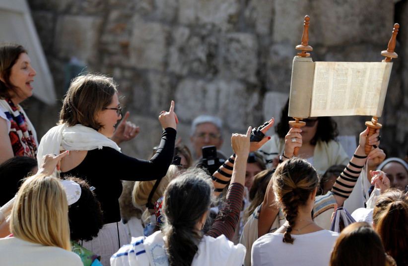 "Members of ""Women of the Wall"" pray with a Torah scroll during a monthly prayer near the Western Wall in Jerusalem's Old City July 24, 2017 (photo credit: REUTERS/Ronen Zvulun)"