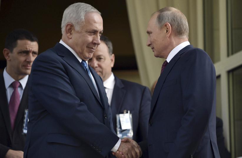 Russian President Vladimir Putin (R) shakes hands with Israeli Prime Minister Benjamin Netanyahu during a meeting in Sochi, Russia August 23, 2017. (photo credit: SPUTNIK/ALEXEI NIKOLSKY/KREMLIN VIA REUTERS)