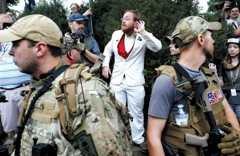 A WHITE nationalist stands behind militia members after he scuffled with a counter demonstrator in Charlottesville, Virginia, August 12. (photo credit: JOSHUA ROBERTS / REUTERS)