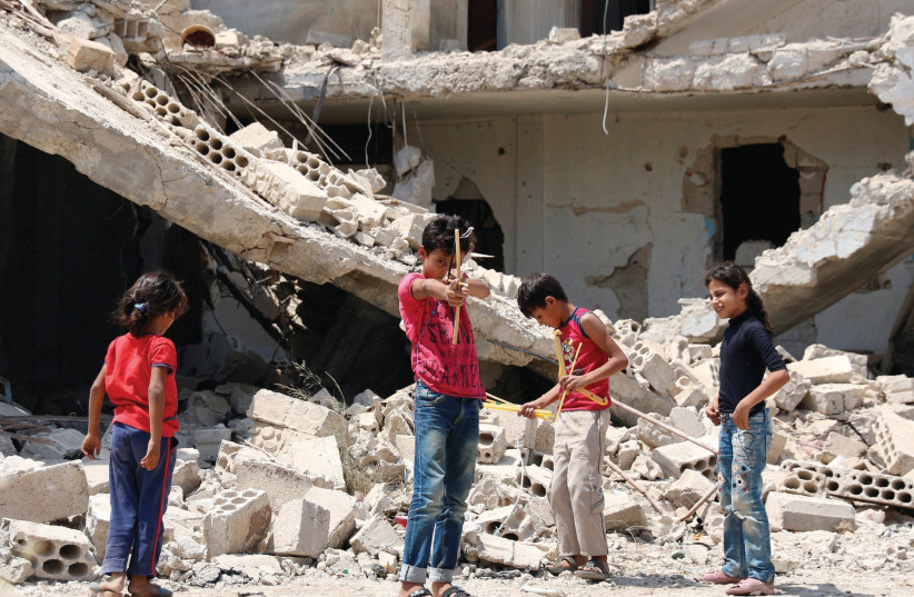 CHILDREN AT play in a rebel-held part of the Syrian city of Deraa on Sunday. (photo credit: ALAA AL-FAKIR / REUTERS)
