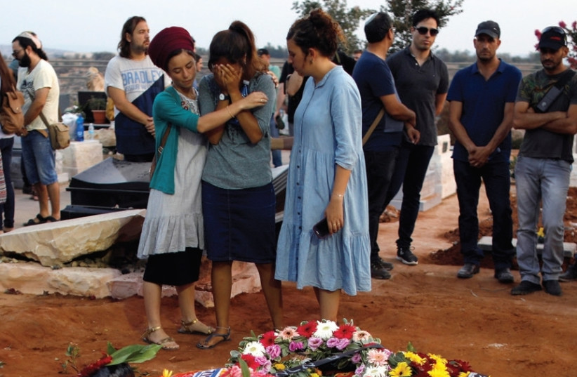 FAMILY AND FRIENDS mourn at the graves of Yosef, Chaya and Elad Salomon, who were buried at the Modi'in Cemetery, on July 23. ( (photo credit: REUTERS)