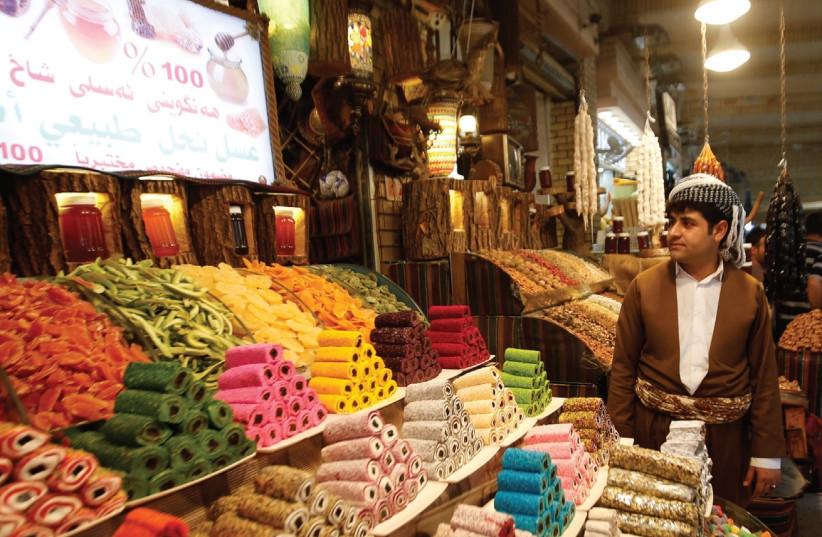 A KURDISH MAN sells traditional candies at market in Erbil, Iraq. (photo credit: REUTERS)