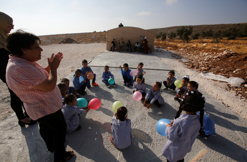 Palestinian schoolchildren play outside a tent where they attend lessons after Israeli troops razed their school building in the West Bank village of Jubbet ad-Dib, near Bethlehem August 24, 2017 (photo credit: REUTERS)