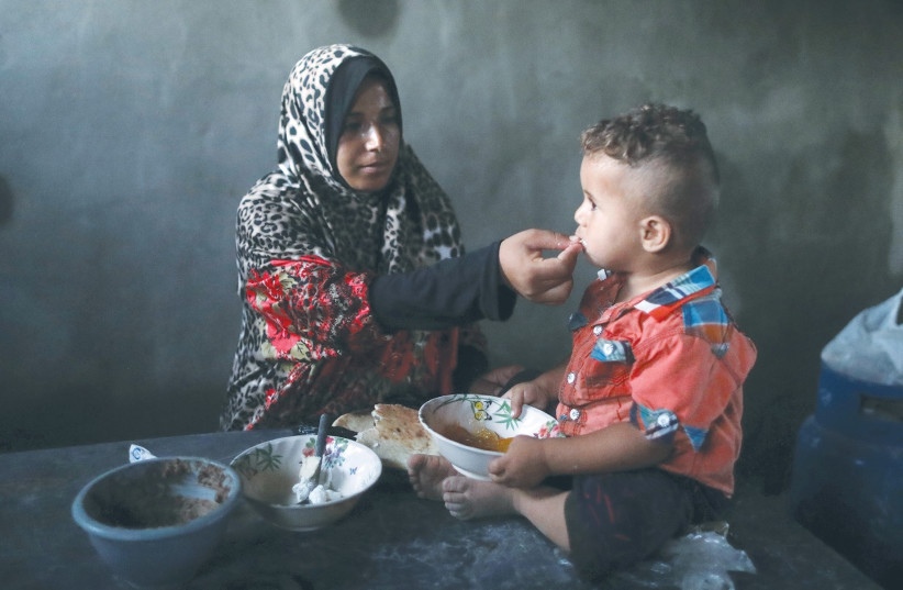 A Palestinian woman feeds her son last month during a power cut in Khan Yunis. (photo credit: MOHAMMED SALEM/ REUTERS)