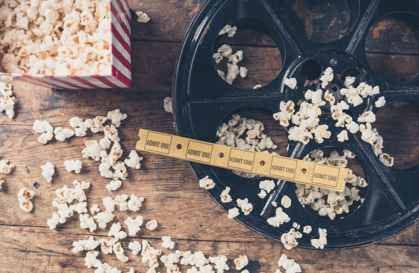 Cinema concept of vintage film reel with popcorn and movie tickets (photo credit: INGIMAGE)