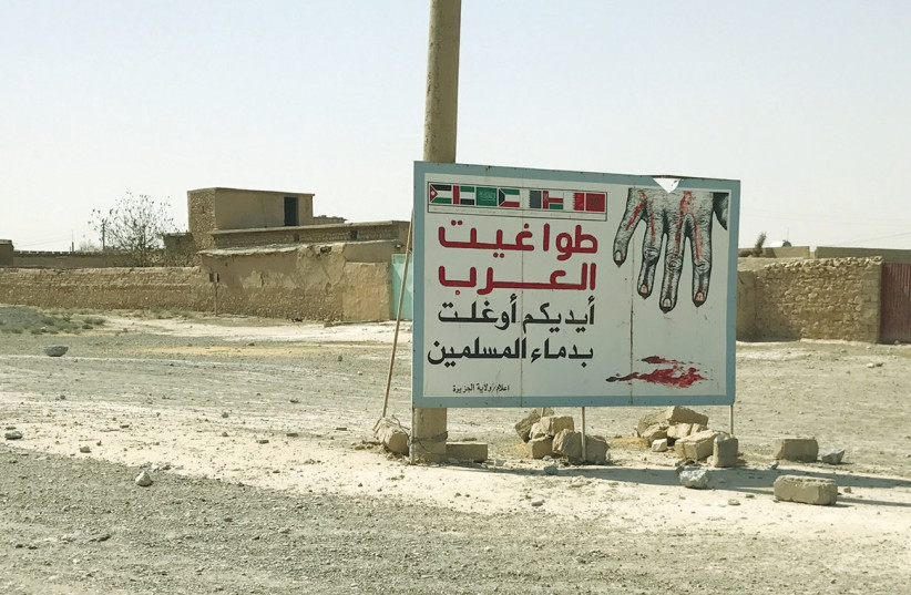 THE SIGN, which says 'Arab tyrants are responsible for the bloodshed of Muslims,' was erected by ISIS on the road to Tel Afar in Iraq. (photo credit: COURTESY MAJD HELOBI)