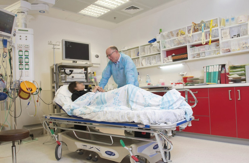 THE SEVEN-YEAR-OLD who nearly lost his life from a massive hemorrhage in his digestive tract speaks with Prof. Ron Shaul, director of the Gastroenterology Institute at Haifa's Rambam Medical Center. (photo credit: RAMBAM HOSPITAL SPOKESMAN)