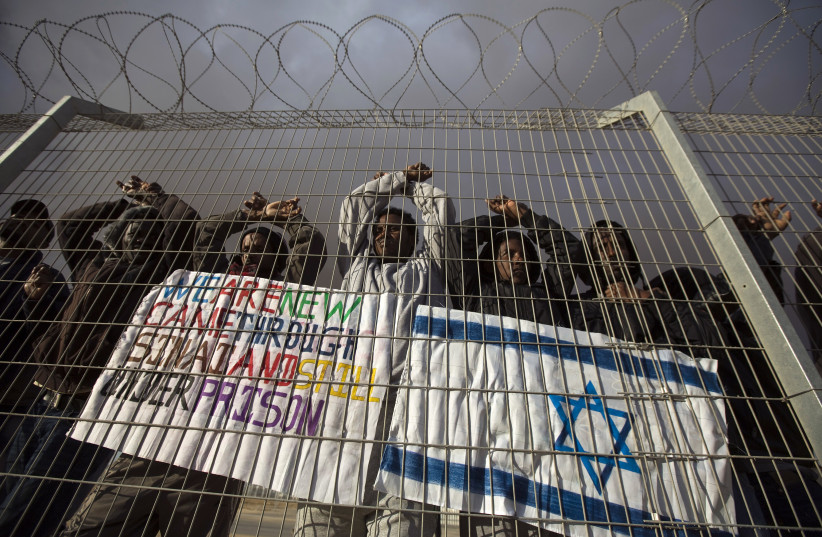 African migrants gesture behind a fence during a protest against Israel's detention policy towards them (photo credit: AMIR COHEN - REUTERS)