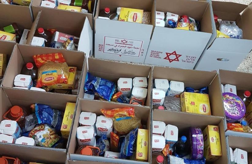 MDS Volunteers pack boxes of food ahead of Eid al-Adha, Summer 2017.. (photo credit: MDA)