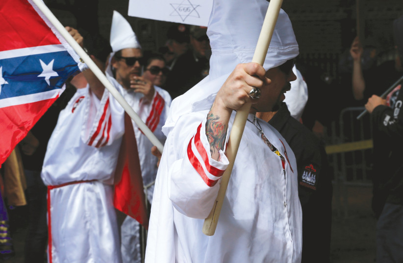 Members of the Ku Klux Klan rally in opposition to city proposals to remove or make changes to Confederate monuments in Charlottesville, Virginia in July. (photo credit: REUTERS)