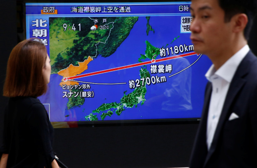 Pedestrians walk past a TV set showing news about North Korea's missile launch in Tokyo, Japan, August 29, 2017 (photo credit: REUTERS)