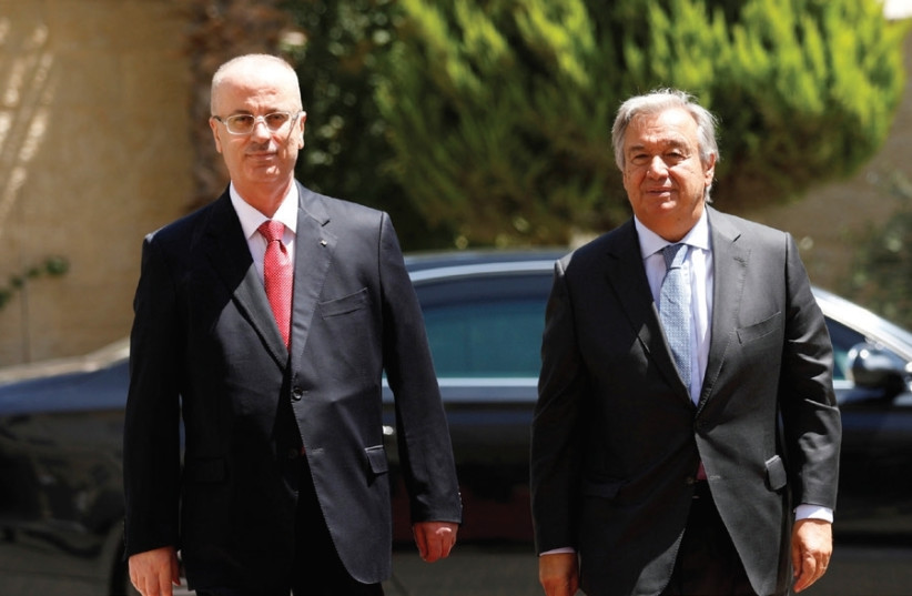 PA Prime Minister Rami Hamdallah (left) walks with UN Secretary-General Antonio Guterres yesterday during a reception ceremony in Ramallah. (photo credit: MOHAMAD TOROKMAN/REUTERS)