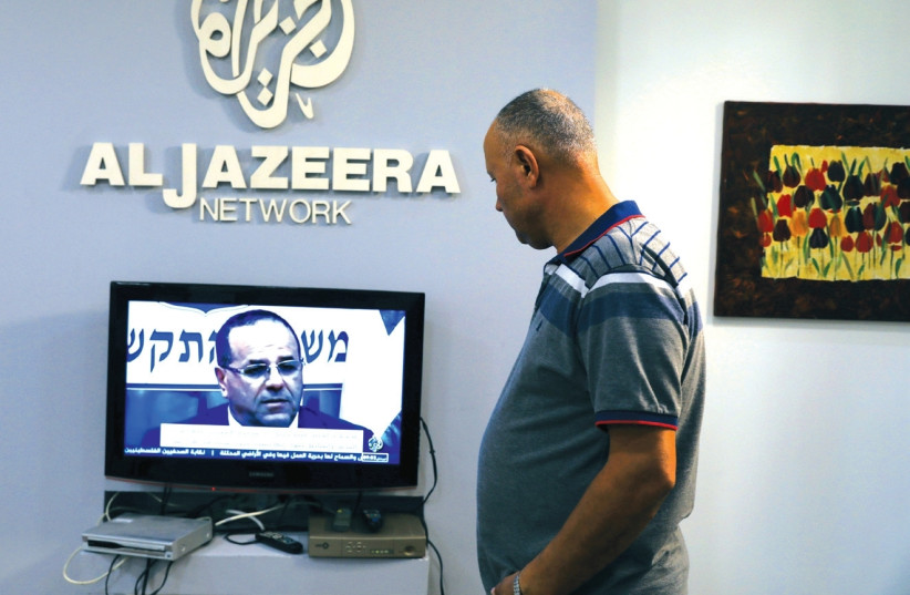AN EMPLOYEE working inside the office of Qatar-based Al- Jazeera network in Jerusalem watches the news, last month. (photo credit: AMMAR AWAD / REUTERS)