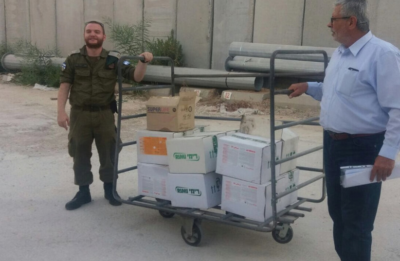 IDF LT. LIOR SHWEITZER (left) prepares the delivery to Gaza of pesticide at a border crossing last week (photo credit: COGAT SPOKESPERSON'S UNIT)