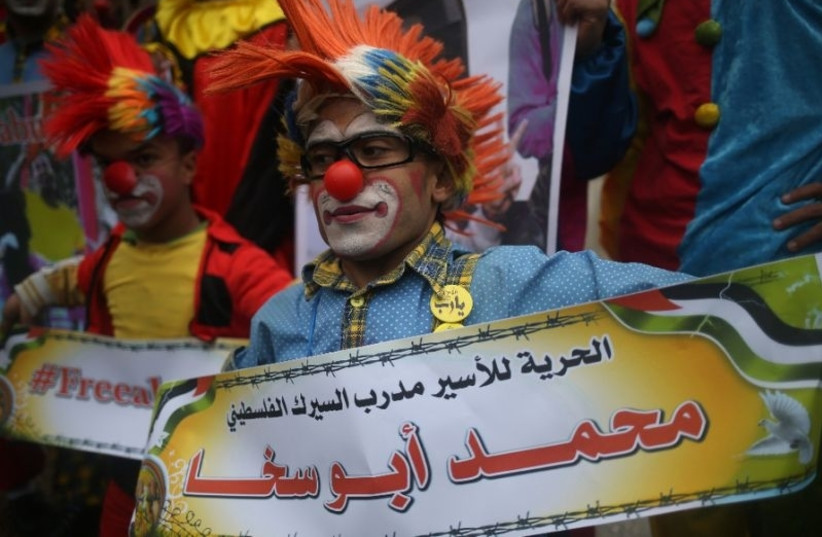 Mohammad Abu Sakha's fellow clowns demontrasted in solidarity with their detained colleague (photo credit: AFP PHOTO/ MOHAMMED ABED)