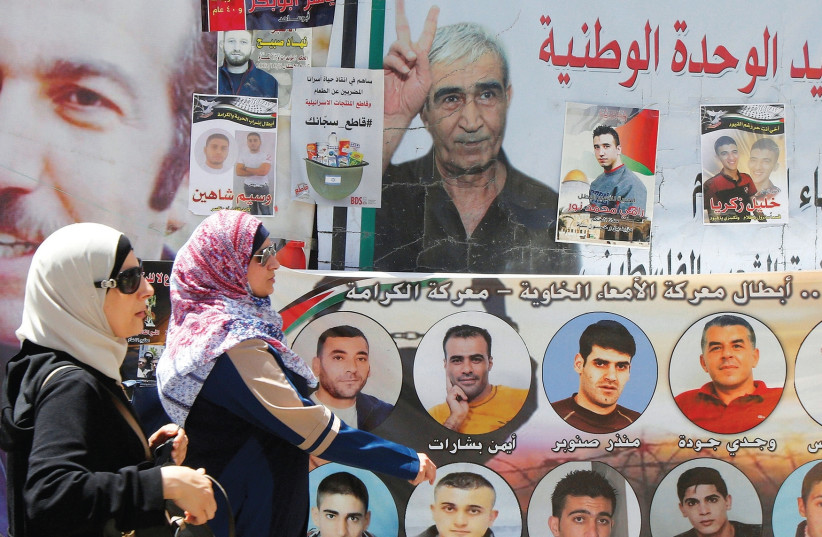 WOMEN WALK past pictures of Palestinian prisoners on hunger strike in Israeli jails, in Nablus in May (photo credit: REUTERS)