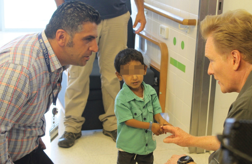 CONAN O'BRIEN speaks to social worker Fares Issa and a wounded Syrian child yesterday at Ziv Medical Center in Safed (photo credit: Courtesy)