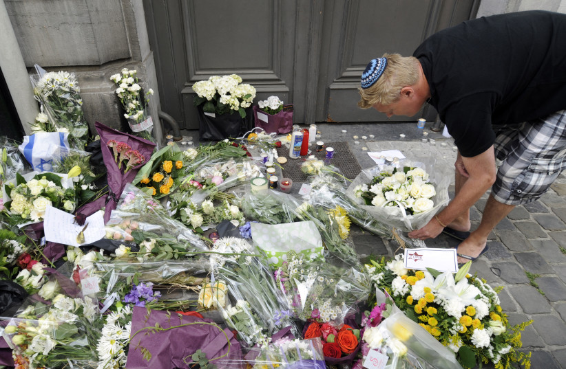 A passer-by puts down flowers at the entrance of the Jewish Museum, site of a shooting in central Brussels May 25, 2014. (photo credit: REUTERS)