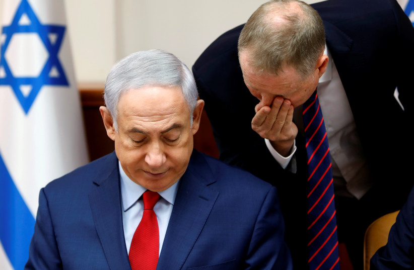 Israeli Prime Minister Benjamin Netanyahu listens to an advisor at the start of the weekly cabinet meeting at his office in Jerusalem August 6, 2017. (photo credit: REUTERS)
