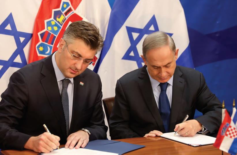 PRIME MINISTER Benjamin Netanyahu and his Croatian counterpart, Andrej Plenkovic, sign a bilateral agreement in Jerusalem in January. (photo credit: REUTERS)