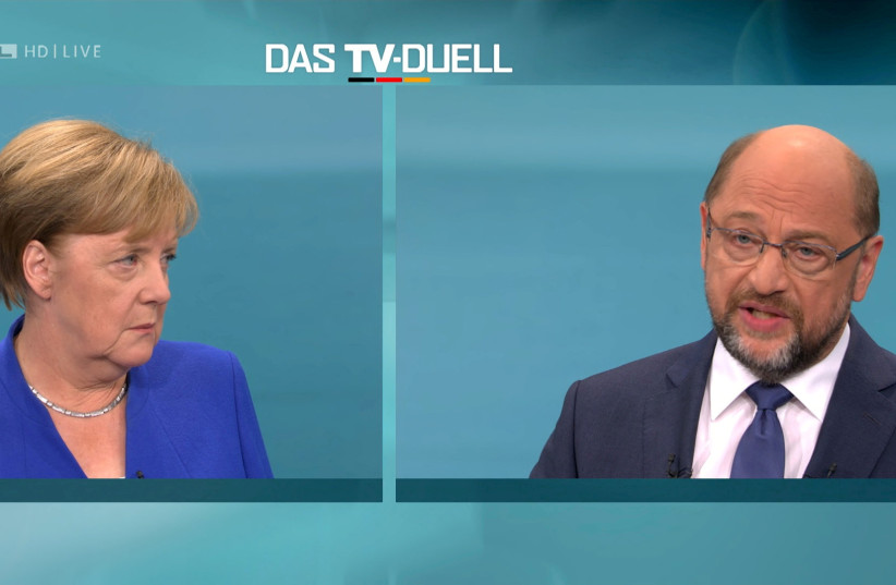 A screen shows the TV debate between German Chancellor Angela Merkel of the Christian Democratic Union (CDU) and her challenger Germany's Social Democratic Party SPD candidate for chancellor Martin Schulz in Berlin, Germany (photo credit: HANDOUT/REUTERS)