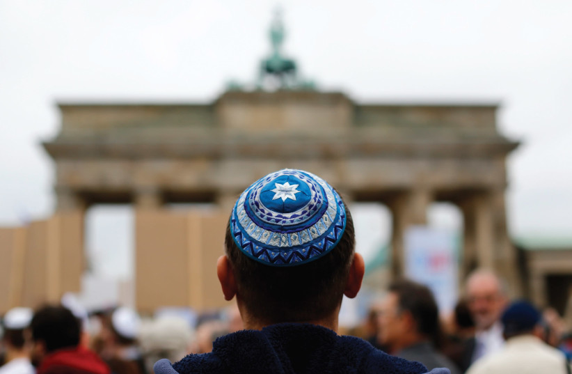 A man wearing a yarmulke looks at the Brandenburg Gate in Berlin. (photo credit: REUTERS)