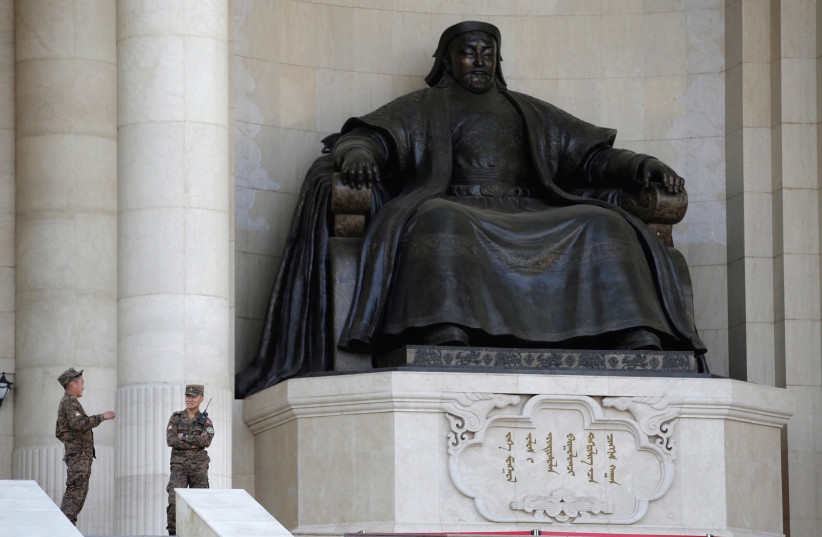 Security personnel chat next to the statue of Genghis Khan at the parliament building in Ulaanbaatar, Mongolia. (photo credit: REUTERS)