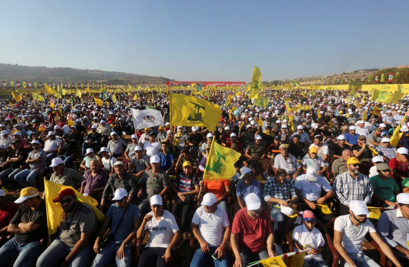 Supporters of Lebanon's Hezbollah leader Sayyed Hassan Nasrallah display Hezbollah flags during a rally marking the 11th anniversary of the end of Hezbollah's 2006 war with Israel, in the southern village of Khiam, Lebanon August 13, 2017. (photo credit: AZIZ TAHER/REUTERS)