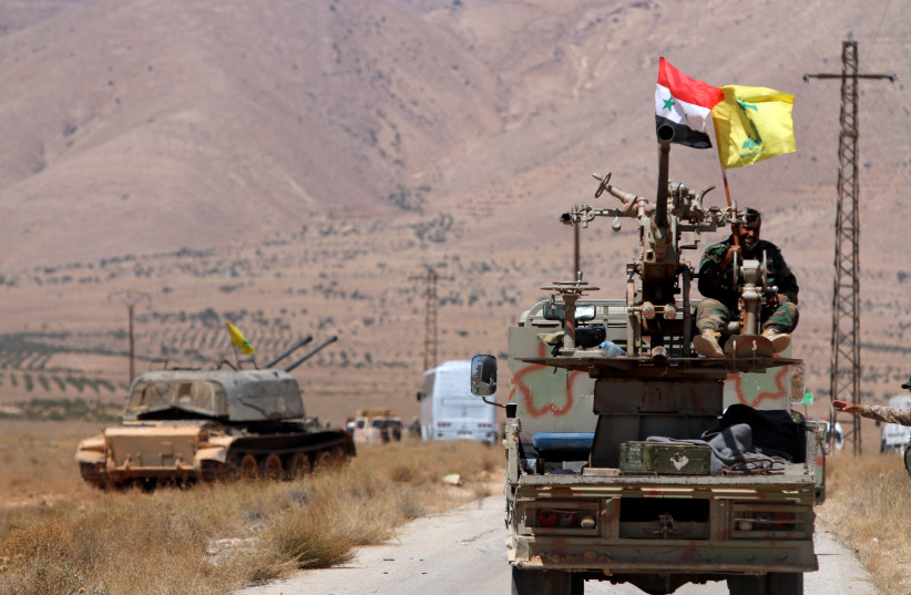 Hezbollah and Syrian flags flutter on a military vehicle in Western Qalamoun, Syria August 28, 2017. (photo credit: OMAR SANADIKI/REUTERS)