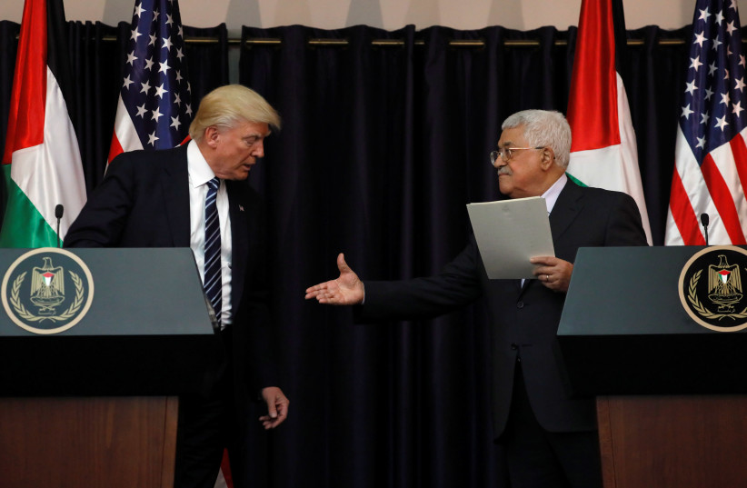 Palestinian President Mahmoud Abbas extends his hand to US President Donald Trump at the Presidential Palace in the West Bank city of Bethlehem May 23, 2017. (photo credit: REUTERS)