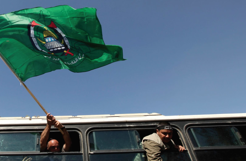A FREED Palestinian prisoner waves a Hamas flag upon his arrival at the Rafah crossing with Egypt in the southern Gaza Strip in October, 2011. (photo credit: REUTERS)
