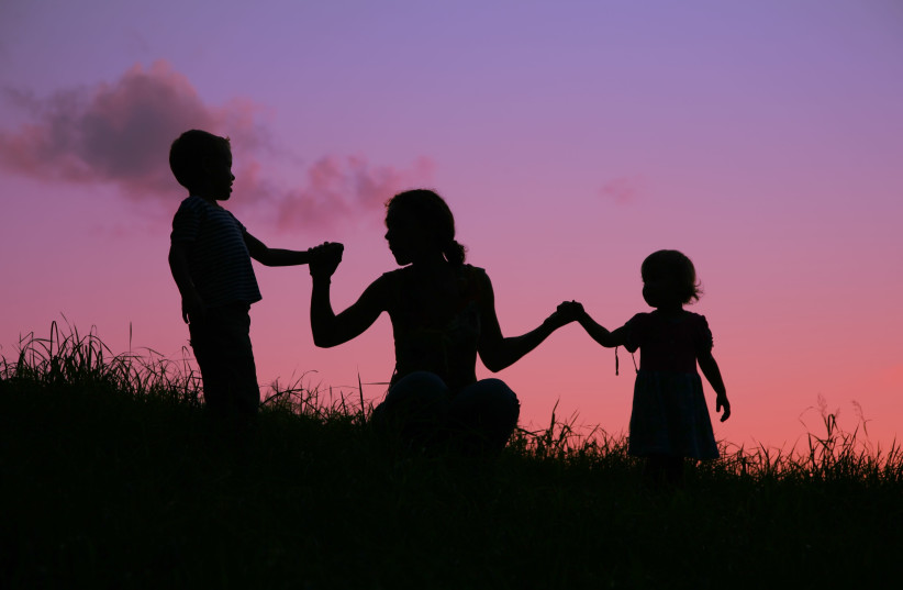 A mother holds two children by the hands during a sunset (photo credit: INGIMAGE)