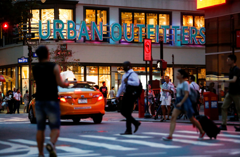 People crosses the street next to the Urban Outfitters store in Manhattan, New York (photo credit: REUTERS/EDUARDO MUNOZ)