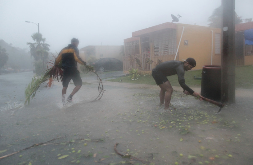 People pick up debris as Hurricane Irma howled past Puerto Rico after thrashing several smaller Caribbean islands, in Fajardo, Puerto Rico September 6, 2017. (photo credit: REUTERS)