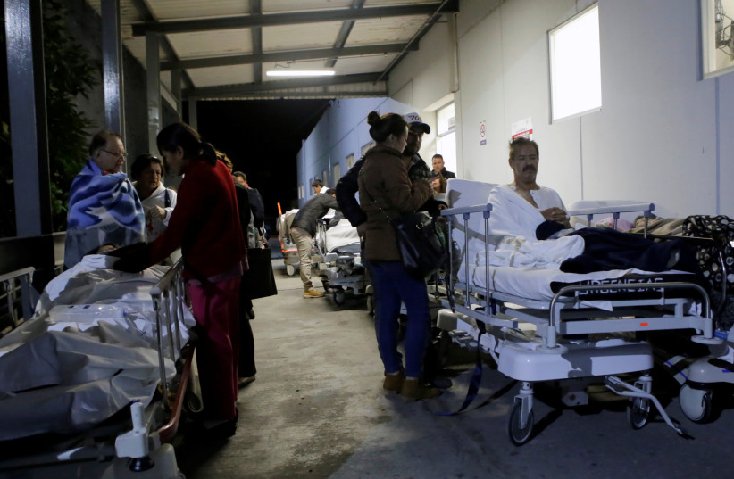 Patients and family members are seen outside the Institute for Social Security and Services for State Workers (ISSSTE) after an earthquake struck off the southern coast of Mexico late on Thursday, in Puebla, Mexico September 8, 2017. (photo credit: REUTERS)