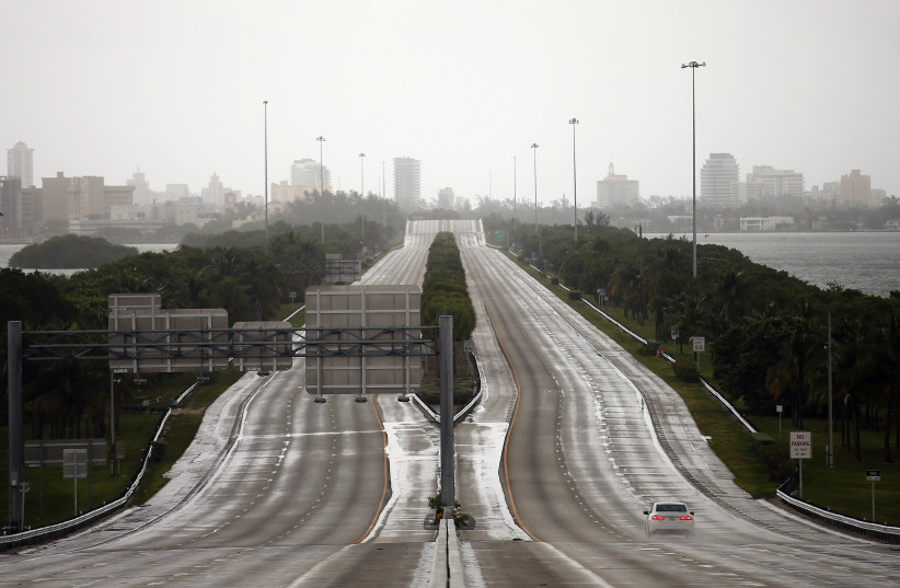 A car drives along an empty highway in Miami before the arrival of Hurricane Irma in south Florida (photo credit: CARLOS BARRIA / REUTERS)