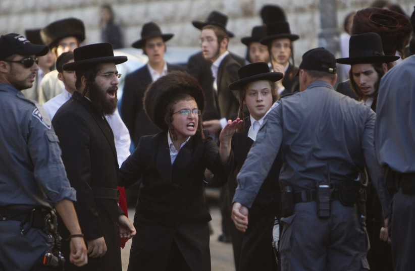 Ultra-Orthodox Jews shout at a policeman during a protest against the opening of a road on the Sabbath, near a religious neighbourhood in Jerusalem June 23, 2012. (photo credit: REUTERS)