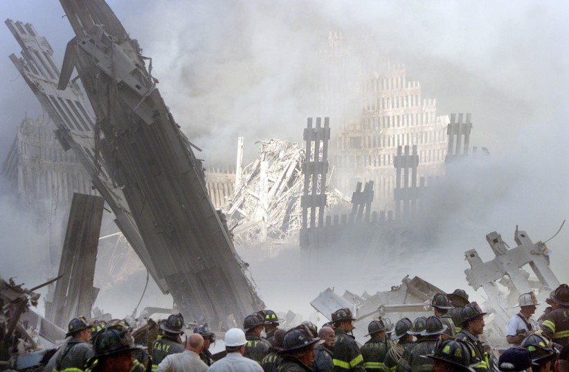 A group of firefighters stand in the street near the destroyed World Trade Center in New York on September 11, 2001. (photo credit: REUTERS)