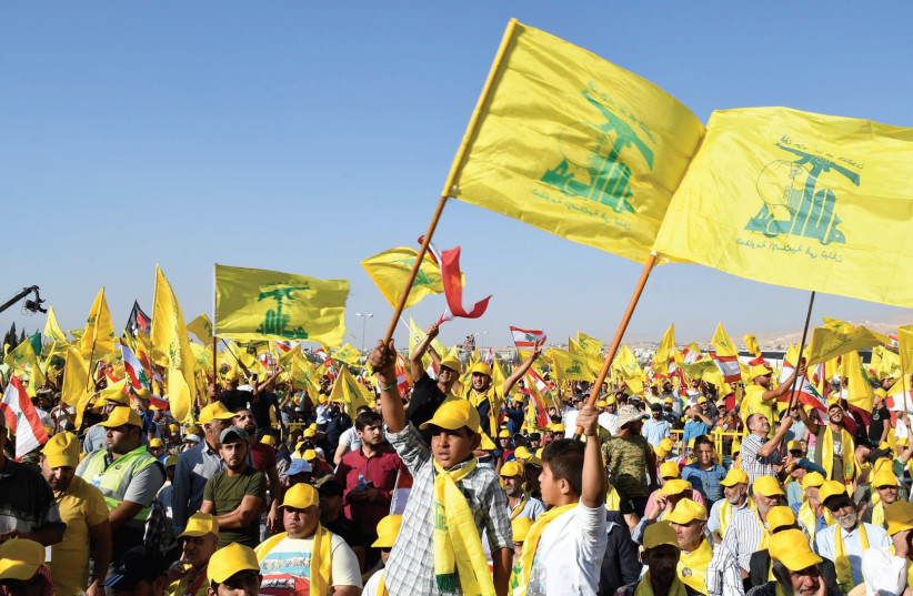 SUPPORTERS OF Hezbollah leader Sayyed Hassan Nasrallah display Hezbollah and Lebanese flags in Lebanon's Bekaa valley.  (photo credit: REUTERS)