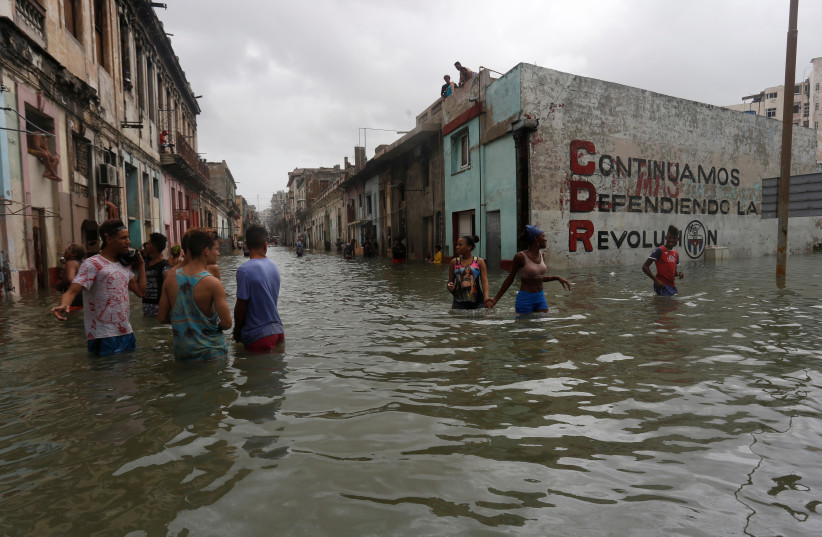 """People wade through a flooded street, after the passing of Hurricane Irma, in Havana, Cuba. The sign on the wall reads """"We will continue to defend the revolution. (photo credit: STRINGER/ REUTERS)"""