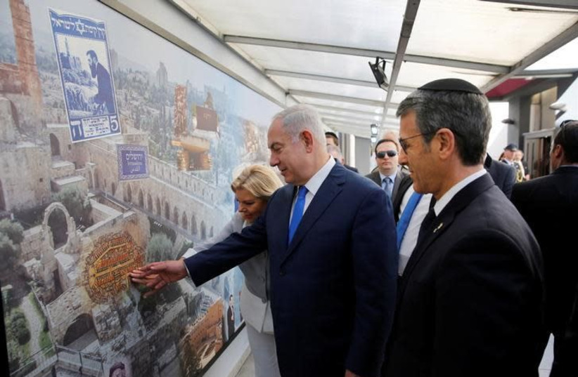 Israeli Prime Minister Benjamin Netanyahu and his wife Sara touch a mural alongside Agustin Zbar, President of the Argentine Israeli Mutual Association (AMIA) Jewish community center, as they visit the AMIA building, which was bombed in 1994, in Buenos Aires, Argentina September 11, 2017. Embassy of (photo credit: HANDOUT/REUTERS)