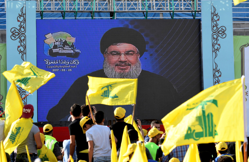Hezbollah leader Sayyed Hassan Nasrallah speaks to supporters on a screen (photo credit: HASSAN ABDALLAH / REUTERS)