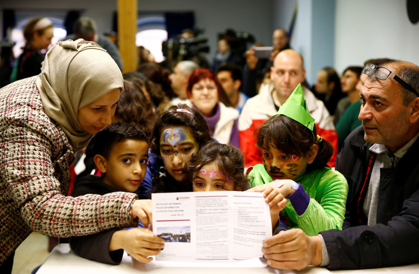 A Syrian family from Palmyra, including children with carnival costumes, read an information leaflet advising on social etiquette for refugees ahead of the carnival season, at a refugee camp in Mainz, Germany February 1, 2016 (photo credit: REUTERS/KAI PFAFFENBACH)