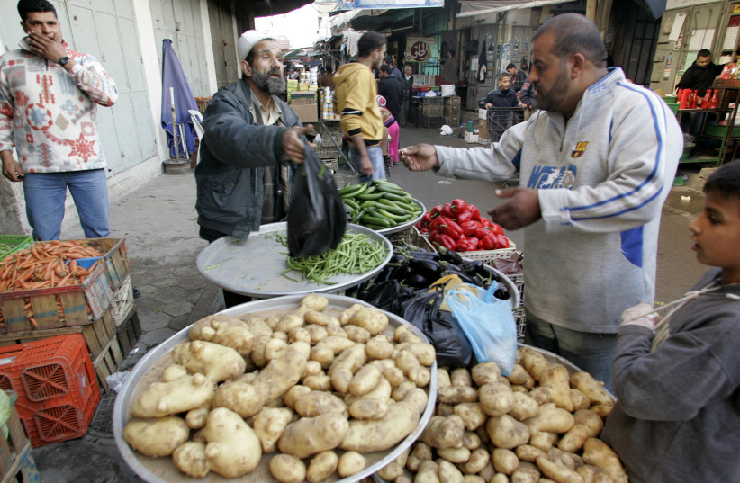 A Palestinian vendor sells vegetables at a market in Gaza City (photo credit: ISMAIL ZAYDAH / REUTERS)