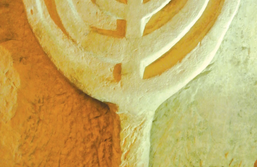 Detail from a catacomb wall and a menorah, at Beit She'arim. (photo credit: SETH J. FRANTZMAN)