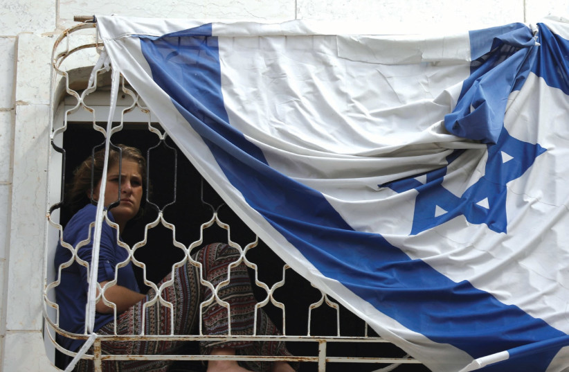 A YOUNG Jewish settler in Hebron looks out of a window in a disputed building. (photo credit: AMIR COHEN - REUTERS)