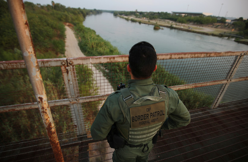 A US border patrol agent looks over the Rio Grande river at the border between United States and Mexico, in Roma, Texas, US, May 11, 2017 (photo credit: REUTERS)