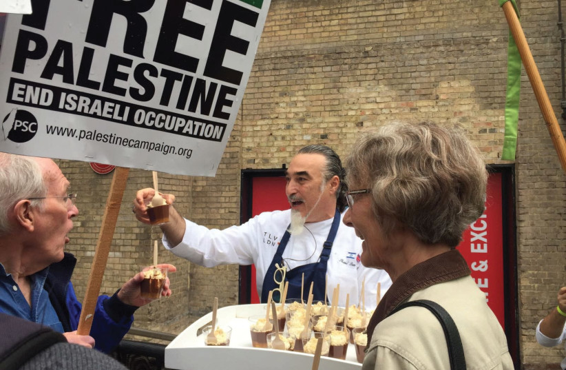 CHEF SHAUL Ben Aderet offers chocolate mousse to BDS protesters outside the Roundhouse Theatre. (photo credit: SHAHAR AZRAN)